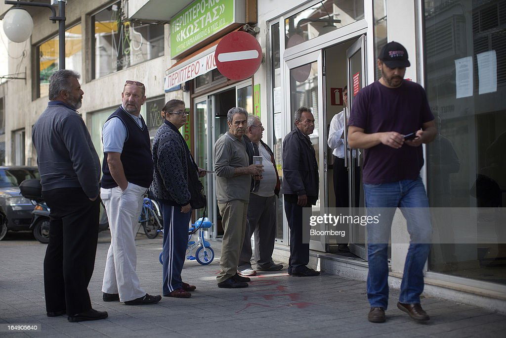 A security guard stands at the door of a Cyprus Popular Bank Pcl, also known as Laiki Bank, as customers wait their turn to enter, in Nicosia, Cyprus, on Friday, March 29, 2013. Cypriots face a second day of bank controls over their use of the euro as officials in Europe urged the country to move quickly to lift the restrictions, the first time they have been imposed on the common currency. Photographer: Simon Dawson/Bloomberg via Getty Images