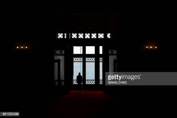 TOPSHOT A security guard stands at the entrance of the Great Hall of the People during the fourth plenary session of the first session of the 13th...