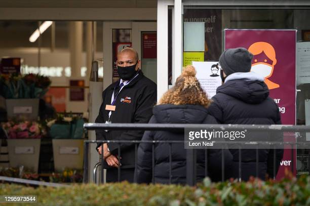 Security guard stands at the entrance to a branch of the Sainsbury's supermarket chain following the company's decision to enforce the mandatory...