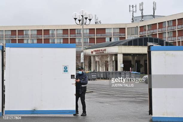 Security guard stands at the gate of the Crowne Plaza hotel which is housing asylum seekers as they wait for their asylum claims to be processed, at...