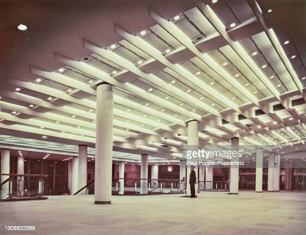 Security guard stands at the top of a staircase in the foyer of the Royal Festival Hall on the South Bank in London circa 1965. The modernist...