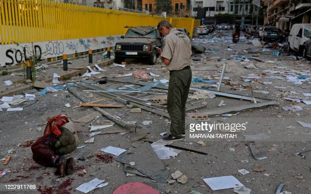 Security guard stands before an injured man lying on the ground amidst debris along a street following an explosion at the port of Lebanon's capital...
