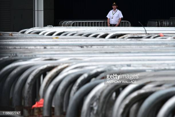 A security guard stands behind rows of barricades outside the Legislative Council in Hong Kong on July 11 after parts of the complex were reopened A...