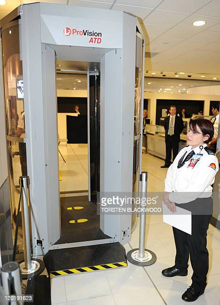 A security guard stands beside Australia's first full body scanner at Sydney International Airport on August 1 2011 A trial using the L3 ProVision...