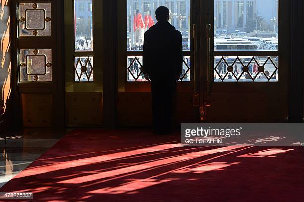 A security guard stands by a gate during the closing ceremony of the Chinese National People's Congress at the Great Hall of the People in Beijing on...