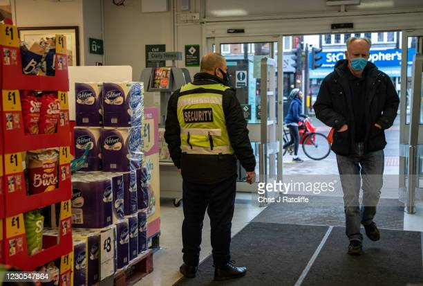 Security guard stands by the entrance to a Morrisons supermarket as a customer wearing a face mask enters the store on January 12, 2021 in London,...