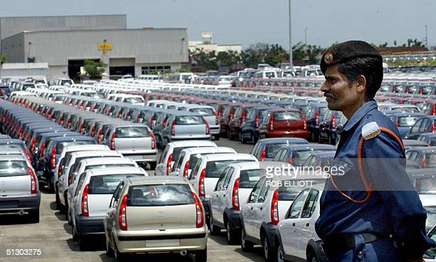 A security guard stands guard near new cars by India's leading automotive manufacturers Tata Motors waiting for shipment at the company's factory in...