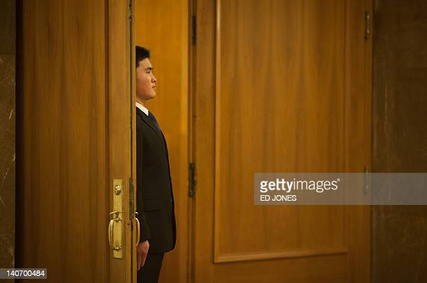 A security guard stands in a doorway to the Great Hall of the People in Tiananmen square during the National People's Congress in Beijing on March 5...