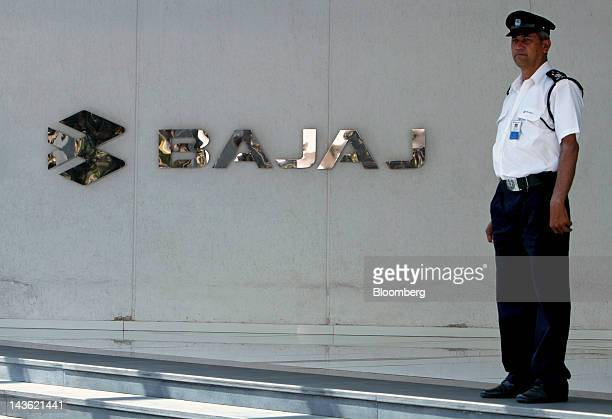 A security guard stands in front of a Bajaj Auto Ltd logo in Pune India on Tuesday Feb 21 2011 Bajaj Auto Ltd is India's No 2 motorcycle maker...