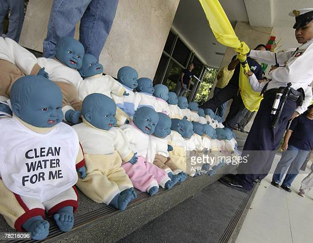 A security guard stands in front of 'blue baby dolls' during a protest on the steps in front of the Department of Environment and Natural Resources...