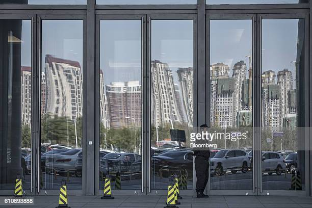 A security guard stands in front of glass doors as traffic and residential buildings are reflected in Tianjin China on Wednesday Sept 28 2016 China's...