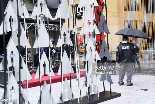 A security guard stands in the rain by the red carpet during preparations for the 90th annual Academy Awards week in Hollywood California on March 2...