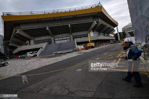 A security guard stands near the Nippon Budokan one of the venues for the Tokyo 2020 Olympic Games in Tokyo on March 27 three days after the historic...