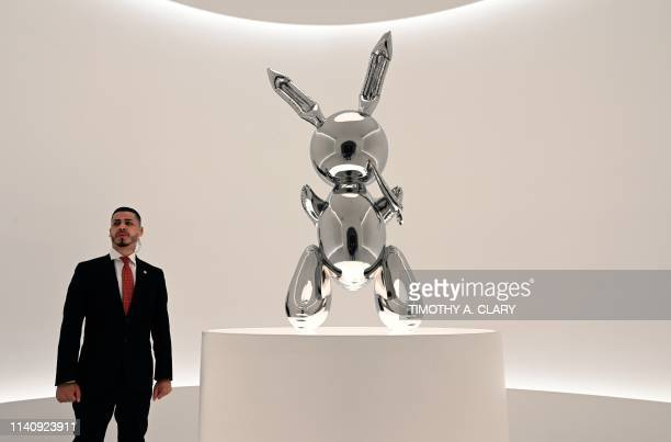 A security guard stands next to Jeff Koons' Rabbit from the Masterpieces from The Collection of SI Newhouse at Christie's New York press preview on...