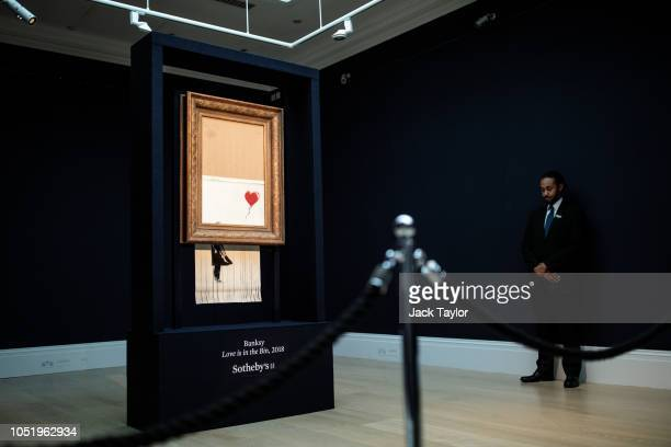 A security guard stands next to 'Love is in the Bin' by British artist Banksy during a media preview at Sotheby's auction house on October 12 2018 in...