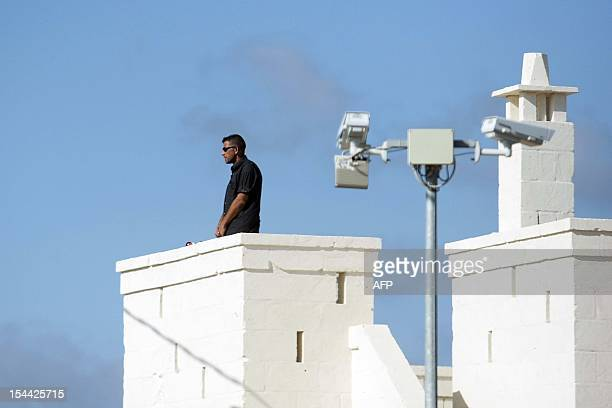 A security guard stands on a roof at the Bagno Egnazia resort in Fasano in the southern Italian region of Puglia where actors Justin Timberlake and...