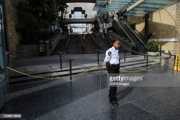 Security guard stands outside a closed shopping center on Hollywood Boulevard to keep pedestrians from entering to prevent the spread of COVID-19. As...