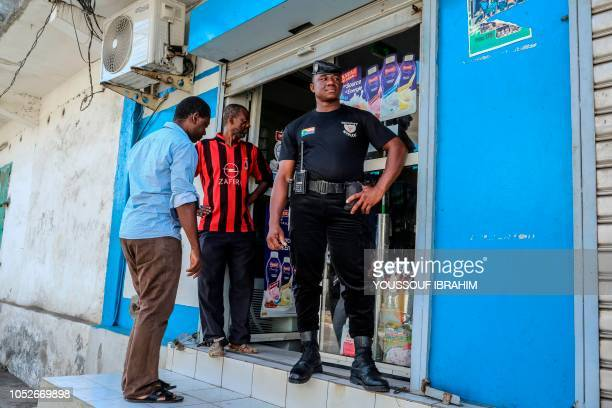 A security guard stands outside a just reopened convenience store in Mutsamudu on October 21 2018 The Comoros military on October 20 regained control...