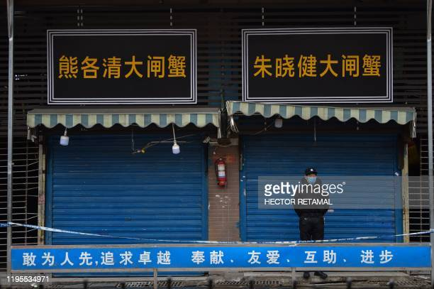TOPSHOT A security guard stands outside the Huanan Seafood Wholesale Market where the coronavirus was detected in Wuhan on January 24 2020 The death...