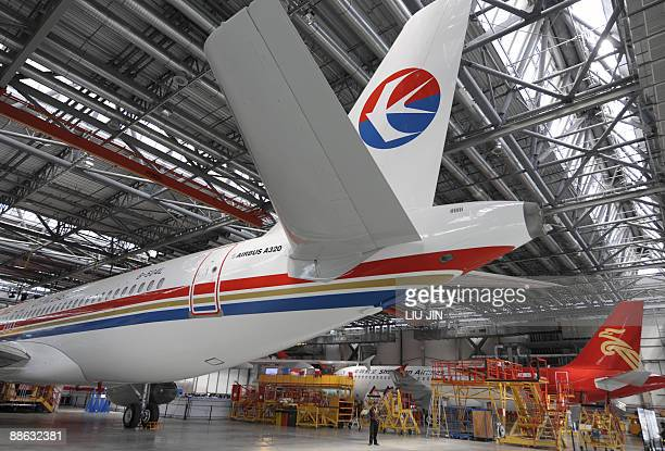 A security guard stands under the tail of an Airbus A320 plane under construction at the Airbus Tianjin plant on June 23 2009 The first completed...