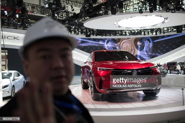 A security guard stops access to a Buick car stand on the eve of the Beijing Auto Show in Beijing on April 24 2018