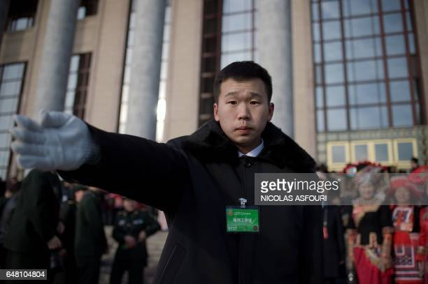A security guard stops journalists as delegates leave the Great Hall of the People at the end of the opening of the National People's Congress in...