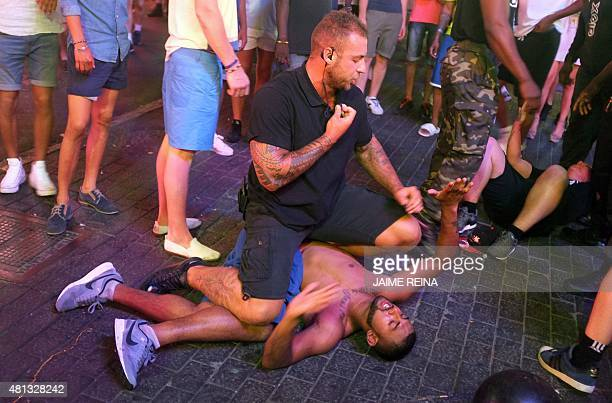 A security guard subdues a man at Punta Ballena street in Magaluf holiday resort in Calvia on the Spanish Mallorca Island on July 19 2014 Known among...