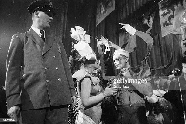 A security guard surveys the revellers in fancy dress at the Dream Ball an Arts Student League Ball held at the Plaza Hotel New York