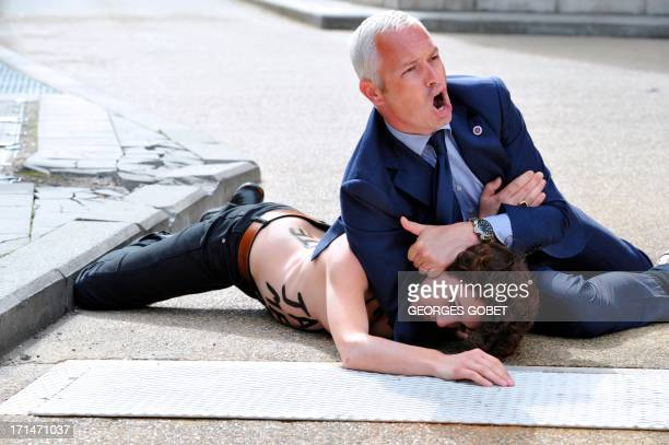 Security guard tackles to the ground a Femen activist as she tried along with two other feminist activists to stop the car of Tunisian Prime Minister...