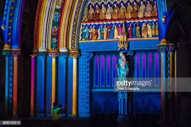 A security guard takes photos of 'The Light of the Spirit Chapter 2' by Patrice Warrener at Westminster Abbey Westminster during Lumiere London...