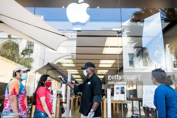 Security guard takes the temperature of a customer outside the Apple Store on May 13, 2020 in Charleston, South Carolina. Customers had their...