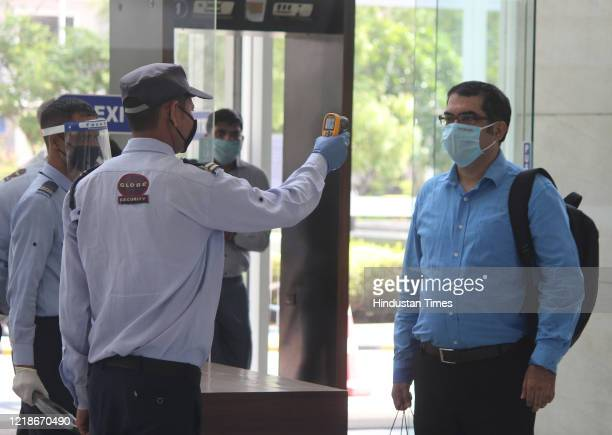 A security guard thermal screens people as they enter an office building at Park Centra in Sector 30 on June 8 2020 in Gurugram India