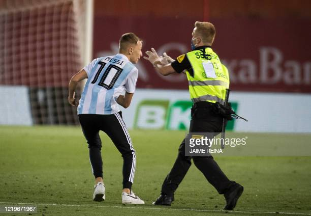 A security guard tries to catch a pitch invader during the Spanish League football match between RCD Mallorca and FC Barcelona at the Visit Mallorca...
