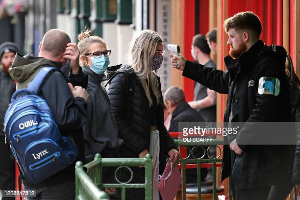 Security guard uses a handheld thermometer to take the temperature of customers, wearing face masks or coverings due to the COVID-19 pandemic, as...