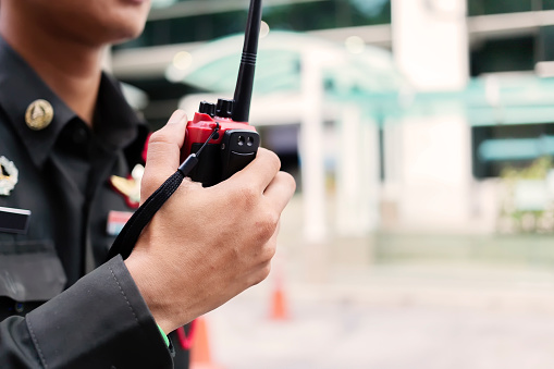 Security guard uses radio communication for facilitate traffic. Traffic Officers use walkie talkie to maintain order in the parking lot in Thailand. 1181040382