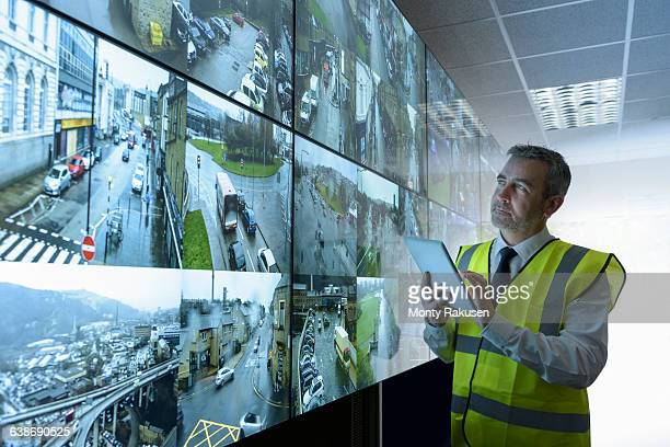 Security guard using digital tablet in security control room with video wall
