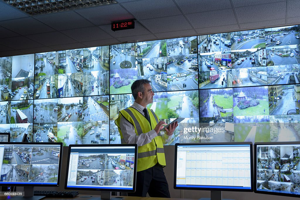 Security guard using digital tablet in security control room with video wall : Stock Photo