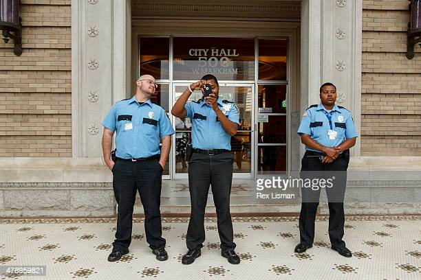 A security guard using his mobile phone to photograph protestors in front of city hall while another security guard looks on