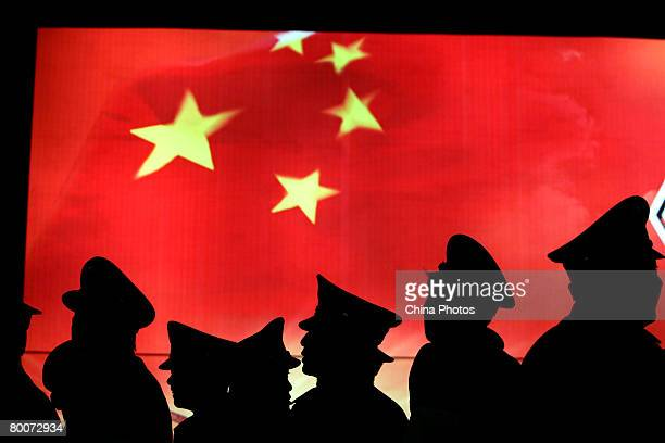 Security guard walk past the Chinese national flag at the Military Museum of Chinese People's Revolution on March 1 2008 in Beijing China From March...