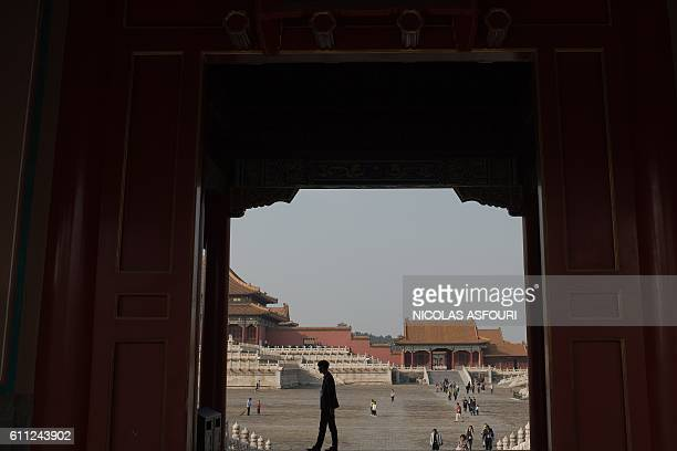 A security guard walks in front of a gate inside the Forbidden City in Beijing on September 29 2016 China celebrates 'Golden Week' on October 1 with...