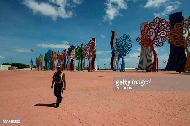A security guard walks in front of the Trees of life at Juan Pablo II square in Managua on April 23 2018 These large metal structures which adorn...