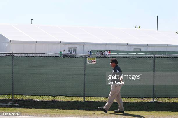 A security guard walks near the fence surrounding the Homestead Temporary Shelter for Unaccompanied Migrant Children facility on February 19 2019 in...