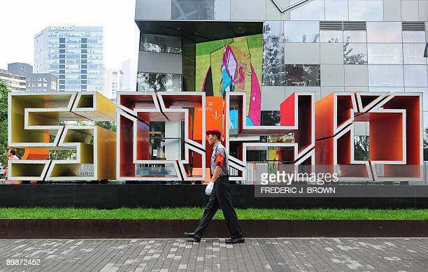 A security guard walks on patrol past a SOHO development in Beijing on August 19 2009 The property developer SOHO China said it has agreed to buy a...