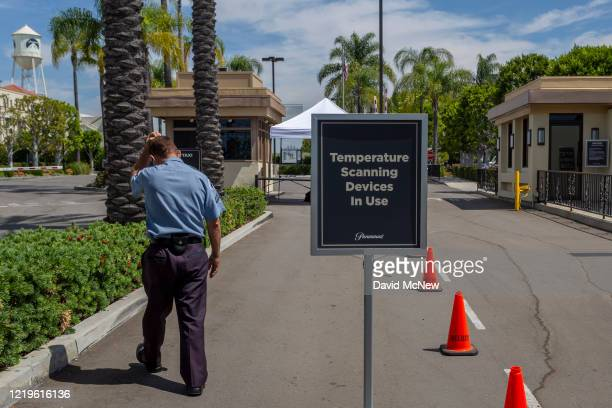 Security guard walks outside Paramount Pictures Studios as Los Angeles County allows more businesses and facilities to reopen today, despite rising...