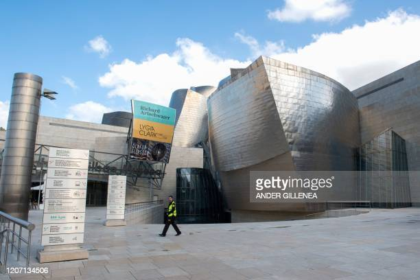 Security guard walks outside the usually overcrowded Guggenheim Bilbao Museum in the Spanish Basque city of Bilbao on March 14, 2020 as Spain...