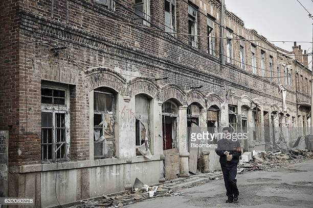 A security guard walks past a derelict building in a neighborhood that is slated for demolition and redevelopment in Dalian China on Wednesday Jan 18...