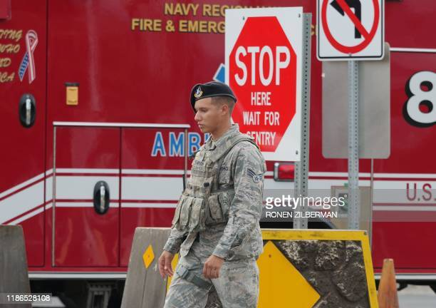 A security guard walks past a naval emergency ambulance responding to a fatal shooting at the Pearl Harbor Naval Shipyard in Honolulu Hawaii on...