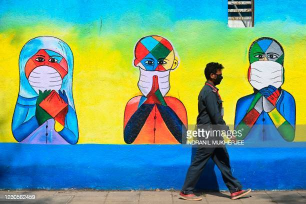 Security guard walks past a wall mural depicting people from various religions thanking frontline Covid-19 coronavirus warriors, in Mumbai on January...