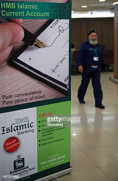 A security guard walks past an advertisement for Islamic banking inside a Habib Metropolitan Bank Ltd branch in Karachi Pakistan on Friday Nov 30...