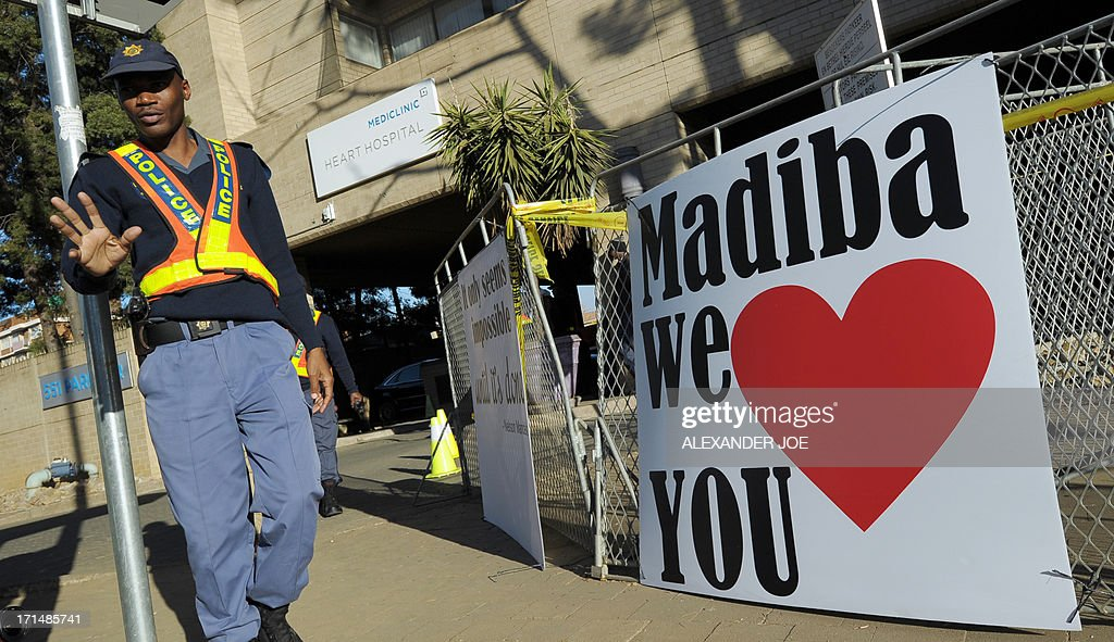 A security guard walks past signs wishing well (R) and quoting (L) former South African president Nelson Mandela on June 25, 2013 outside of the Mediclinic heart hospital in Pretoria where Mandela is receiving treatment. Mandela's close family gathered today at his rural homestead to discuss the failing health of the South African anti-apartheid icon who was fighting for his life in hospital. Messages of support poured in from around the world for the Nobel Peace Prize winner, who spent 27 years behind bars for his struggle under white minority rule and went on to become South Africa's first black president.